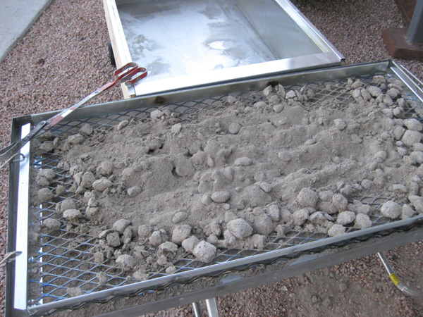 Coal tray resting on metal handles