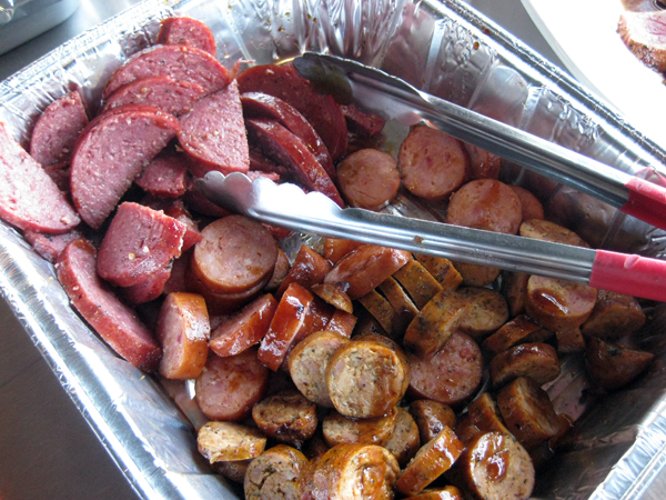 The assorted sausages were sliced and sauced.